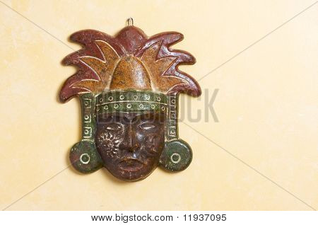 Ornate Myan Mask Hanging on a Light Yellow Wall
