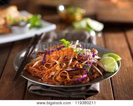 beef pad thai stir fry dish on plate with chopsticks