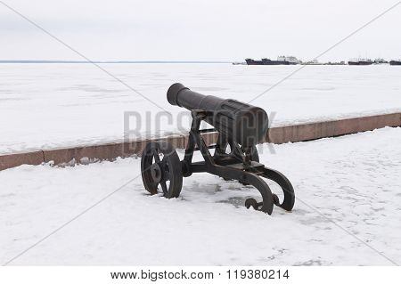 Old cast iron cannon on a winter snow-covered embankment