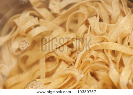 Closeup Of Homemade Raw Noodles From Spelt Dough Cooking In Boiling Water.