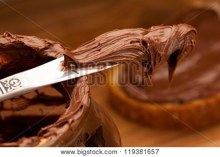 Knife Full Of Sweet Chocolate Nougat Spread On Glass Jar.