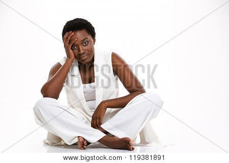 Tired pretty african american young woman sitting with legs crossed and having headache over white background