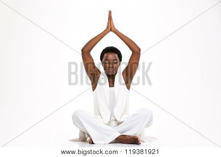 Attractive calm african american young woman with eyes closed sitting in lotus pose and meditating over white background