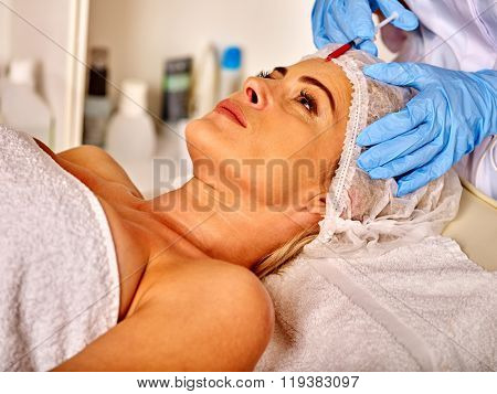 Lying woman middle-aged in spa salon with beautician. Beauty woman gets anti age injections.