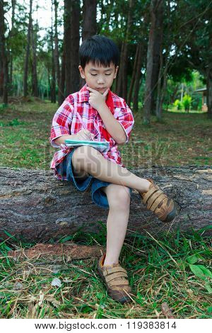 Full Body. Asisn Child Thoughtful On Wooden Log In National Park. Outdoors. Education Concept.