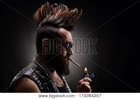 Young man with a Mohawk hairstyle and a leather jacket lighting up a cigarette on dark background