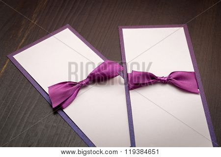 Two Handmade Cards With Purple Satin Tape On Wood Background