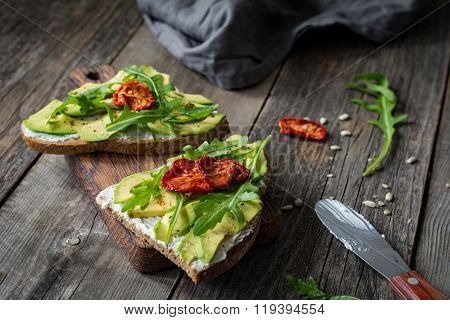 Healthy avocado toast with white cheese and arugula