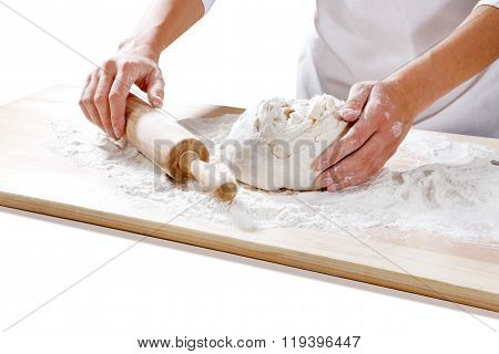female hands taking rolling pin for making dough