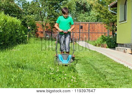 Boy Cutting Grass Around The House In Summertime