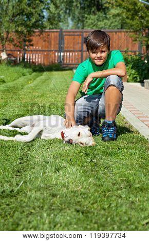 Boy Petting His Young Labrador Retriever Dog