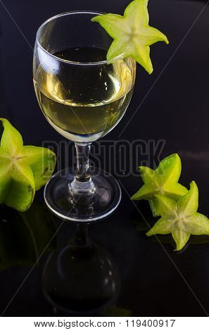 fresh starfruit and a drink in a glass on black background