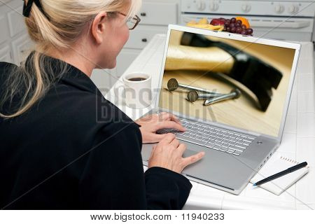 Woman In Kitchen Using Laptop to Research Home Improvement. Screen image can easily be replaced using the included clipping path.