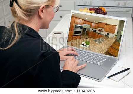 Woman In Kitchen Using Laptop to Research Home Improvement Ideas. Screen image can easily be replaced using the included clipping path.