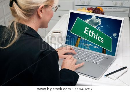Woman In Kitchen Using Laptop with Ethics Road Sign on Screen. Screen image can easily be replaced using the included clipping path.