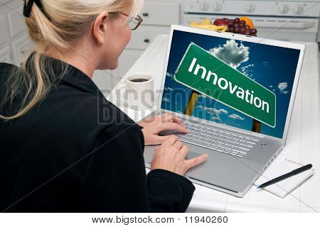Woman In Kitchen Using Laptop with Innovation Road Sign on Screen. Screen image can easily be replaced using the included clipping path.