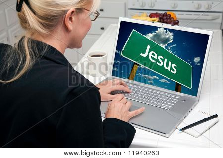 Woman In Kitchen Using Laptop with Jesus Road Sign on Screen. Screen image can easily be replaced using the included clipping path.