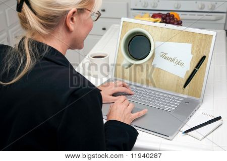 Woman In Kitchen Using Laptop with Thank You Image on Screen. Screen image can easily be replaced using the included clipping path.