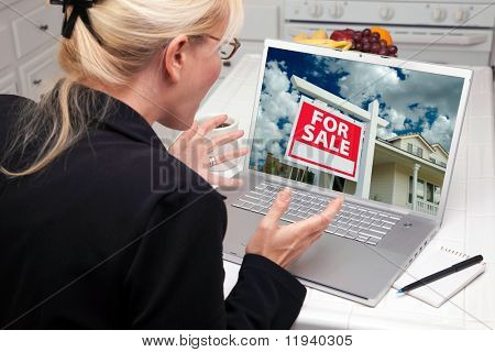Excited Woman In Kitchen Using Laptop to Buy a Home. Screen image can easily be replaced using the included clipping path.