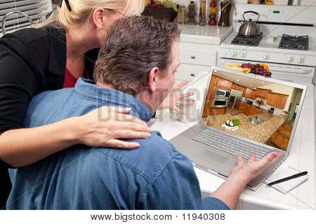 Couple In Kitchen Using Laptop to Research Home Improvement Ideas. Screen image can easily be replaced using the included clipping path.