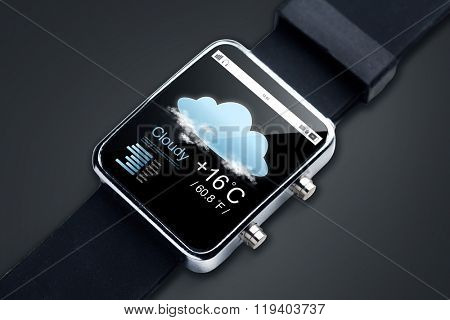 modern technology, objectm, weather and media concept - close up of black smart watch with forecast app and air temerature on screen