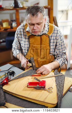 Man upholstering chair in his workshop