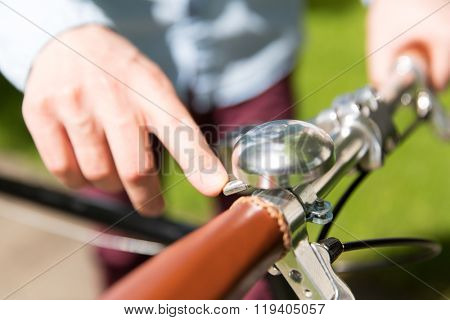 people, style, leisure and lifestyle - close up of male hand ringing retro ding dong bicycle bell on fixed gear bike wheel