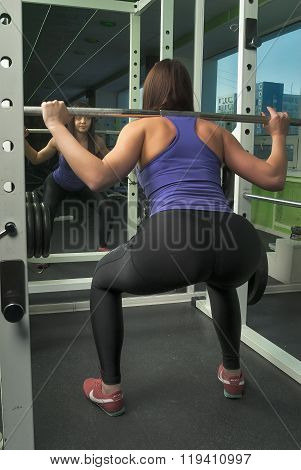 Woman doing shoulder exercise with weight bar