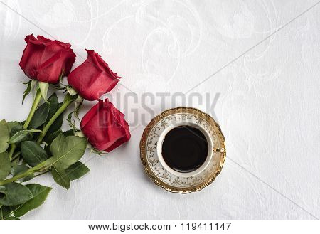 cup of coffee with three red roses on a white background