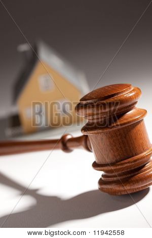 Gavel and Model Home on Gradated Background with Selective Focus.
