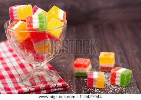 Colorful jelly candy in a glass vase on  wooden background