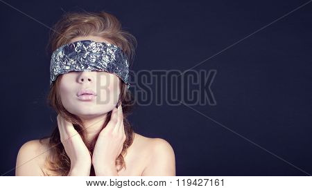 Mysterious beautiful woman with ribbon on eyes