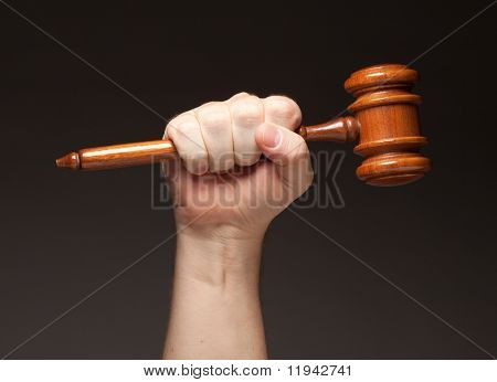 Male Fist Holding Wooden Gavel on a Grey Background.