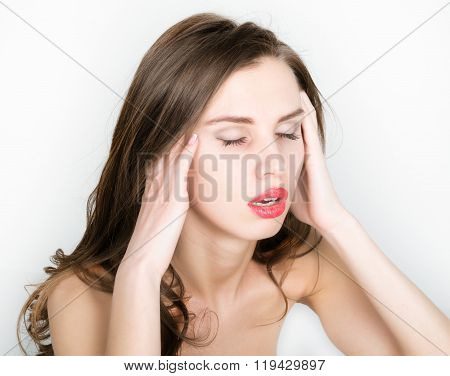 Beautiful woman holds a head, suffering from a headache. migraine