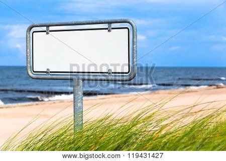 Metal made signpost with blank white billboard at a summery beach