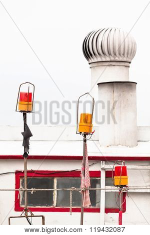 Three red and orange nostalgic rotation beacon lamps with different sizes in front of a boat cabin window and ventilation shaft at the roof