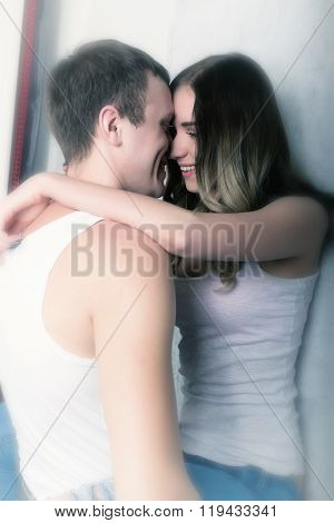 Happy young couple enjoying an intimate moment, laughing a lot and man gently strokes his partner's