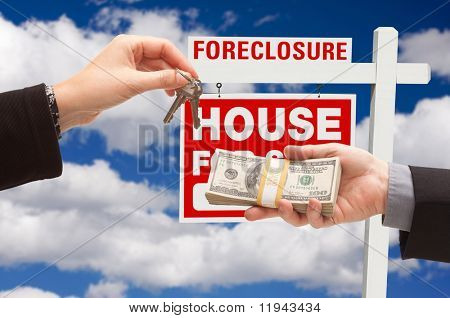Handing Over Cash For House Keys in Front of Foreclosure Sign and Cloudy Blue Sky.
