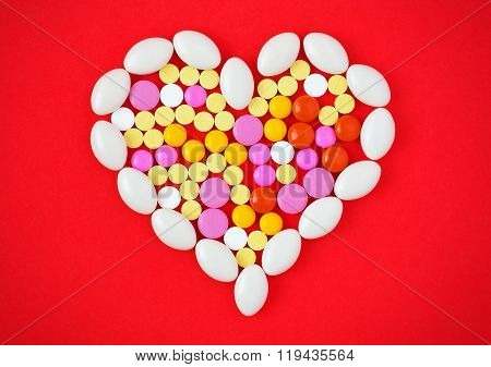 Colorful Tablets Arranged In A Heart Shape On Red Background. Symbol Photo Of Heart Disease, Medicat