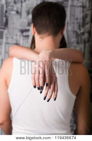 girl tenderly embraces the man's neck, girl's hands only seen