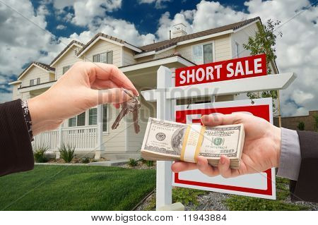 Handing Over Cash For House Keys and Short Sale Real Estate Sign in Front of Home.