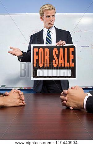 Businessman holding for sale sign
