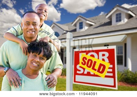 Happy and Attractive African American Family with Sold For Sale Real Estate Sign and House.