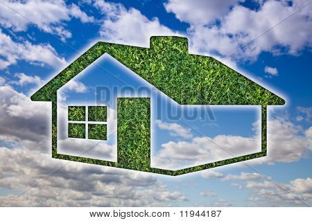 Green Grass House Icon Over Blue Sky and Clouds.