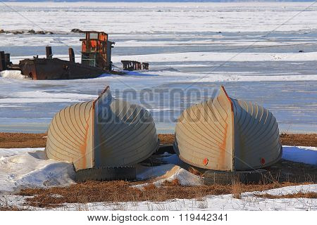 rowing boats lie on the shore of the frozen sea