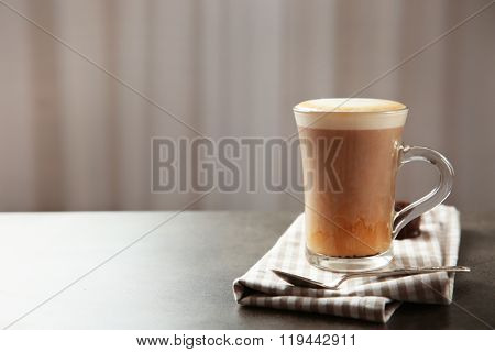 Milk coffee in glass cup and spoon on grey table