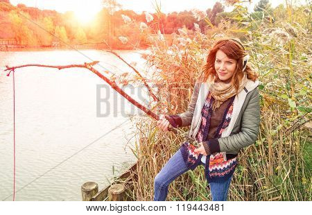 Young Model Woman With Earmuffs Playing On Lake Shore - Teenager Girl On Winter trip Having Fun -