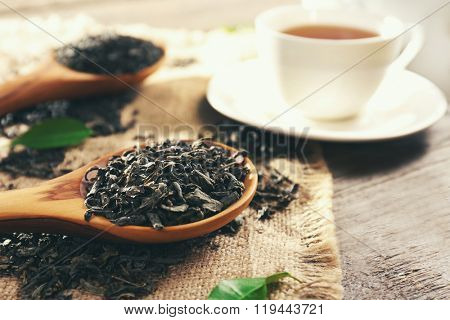 Still life with granulated tea and green leaves on wooden table closeup
