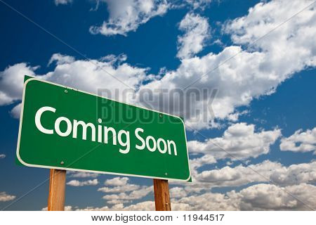 Coming Soon Green Road Sign with Copy Room Over The Dramatic Clouds and Sky.