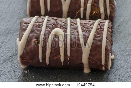 Chocolate swiss roll close up dessert on black